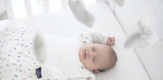 Träumeland: Baby schläft glücklich im Babybett.